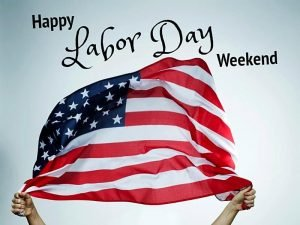American flag held in two hands with text Happy Labor Day Weekend